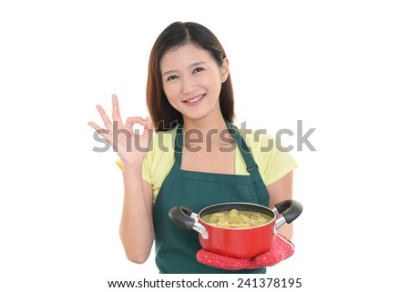 Young woman wearing kitchen apron with pot - stock photo
