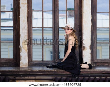 Young woman wearing long black dress and hat posing on windowsill. Retro style pictures