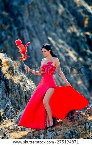 young woman wearing long red dress and mask - stock photo