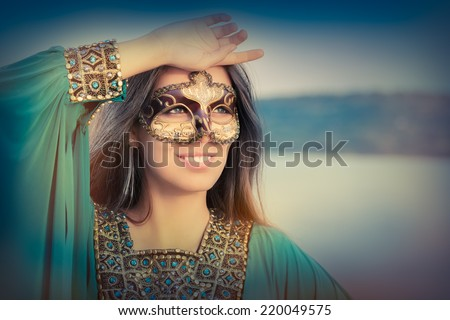 Young Woman Wearing Mask  and Oriental Dress - Portrait of a masked glamour woman - stock photo