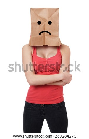young woman wearing paper bag with sad smiley face over her head - stock photo