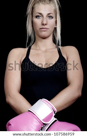 young woman wearing pink boxing gloves and ready to attack - colorized photo - stock photo