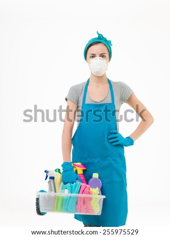 young woman wearing protection mask and holding basket with cleaning supplies, on white background - stock photo