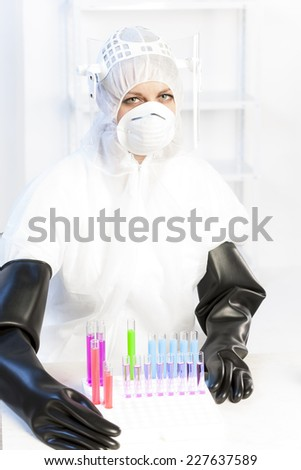 young woman wearing protective clothes in laboratory - stock photo