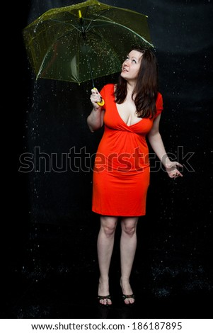 Young woman wearing red dress stands under an umbrella - stock photo