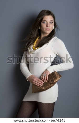 Young woman wearing short white dress standing against gray wall. - stock photo