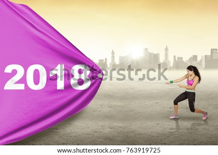 Young woman wearing sportswear while pulling numbers 2018 in a banner with city background