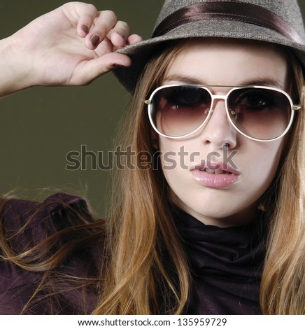 Young woman wearing sunglasses against dark background - stock photo