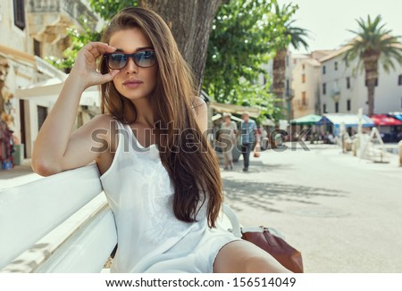 Young woman wearing sunglasses and resting on bench - stock photo