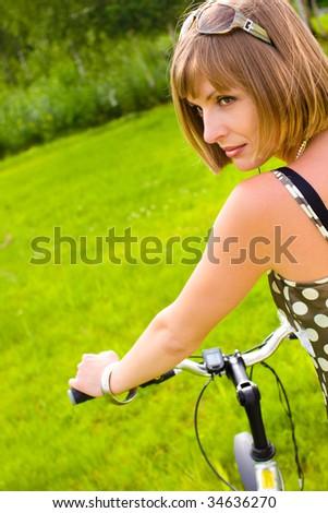 Young woman wearing sunglasses holding a bike - stock photo