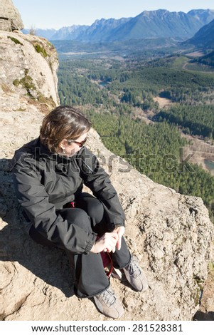 Young woman wearing sunglasses sitting on a rocky outcrop enjoying the view of the forested valley, lake and mountains from Rattlesnake Ledge Trail, Snoqualmie, Washington after hiking up the summit - stock photo