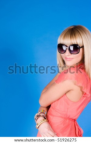 Young woman wearing the big modern sunglasses. Studio shot on a blue background