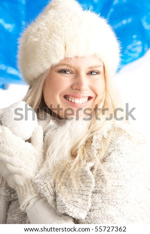 Young Woman Wearing Warm Winter Clothes And Fur Hat Holding Snowball In Studio - stock photo