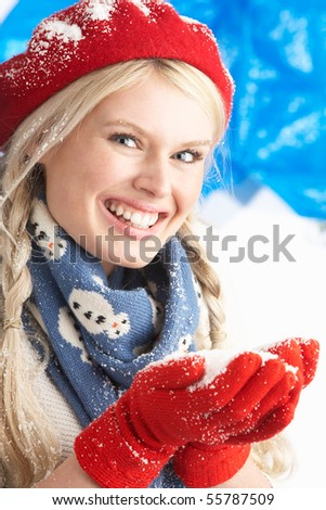 Young Woman Wearing Warm Winter Clothes And Hat Holding Snow In Studio - stock photo