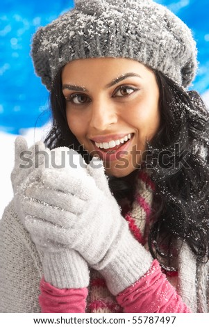 Young Woman Wearing Warm Winter Clothes And Hat Holding Snowball In Studio - stock photo