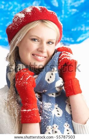 Young Woman Wearing Warm Winter Clothes And Hat In Studio - stock photo