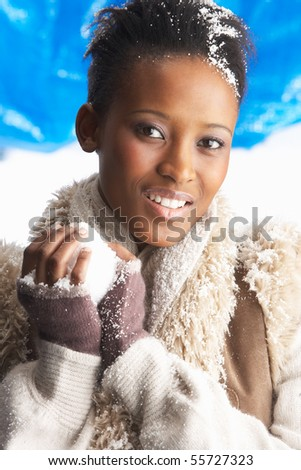 Young Woman Wearing Warm Winter Clothes Holding Snowball In Studio - stock photo