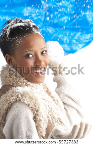 Young Woman Wearing Warm Winter Clothes Throwing Snowball In Studio