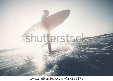 Young woman wearing wetsuit, holding surfboard under her arm and entering ocean waves for evening (or morning) surfing session  - stock photo