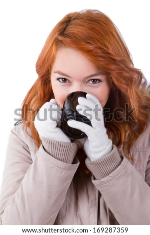 Young woman wearing winter clothes and drinking hot drink from a cup, isolated on white background. - stock photo