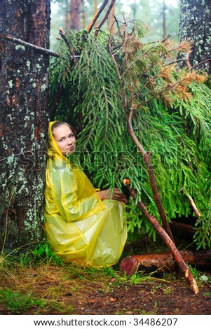 Young woman wearing yellow  raincoat sitting in a shelter of branches - stock photo