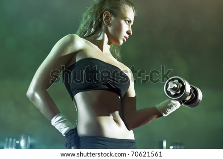 Young woman weight training. Focus on face. - stock photo