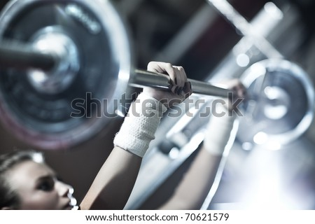 Young woman weight training. Focus on hand.
