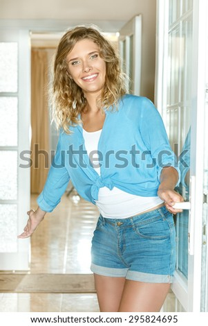 Young woman welcoming people at entrance door - stock photo