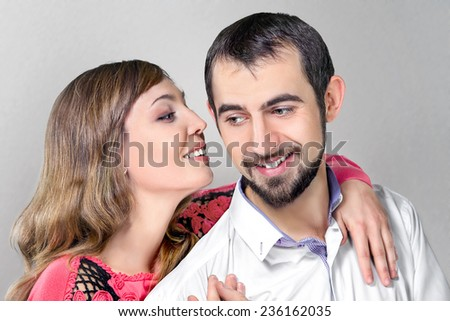 Young woman whisper to boyfriend putting a hand on his shoulder - stock photo
