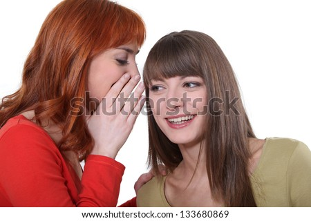 Young woman whispering a secret into her friend's ear - stock photo
