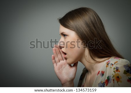 Young woman whispering something - stock photo