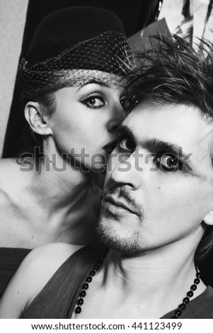 Young woman whispers something in the ear of a man - stock photo
