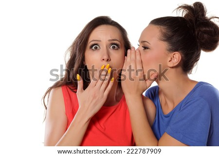 young woman whispers to her mate shocking news - stock photo