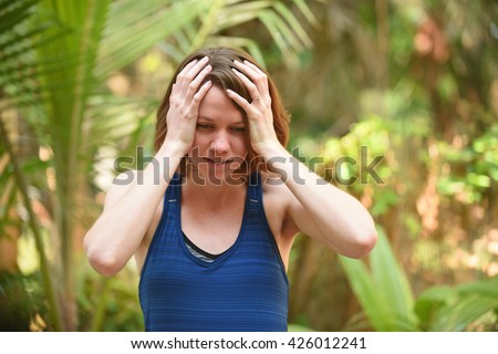 Young woman who is frustrated or worried with hands on head to express stress - stock photo