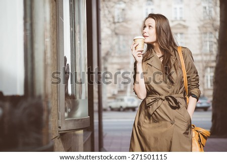 Young woman window shopping and drinking coffee