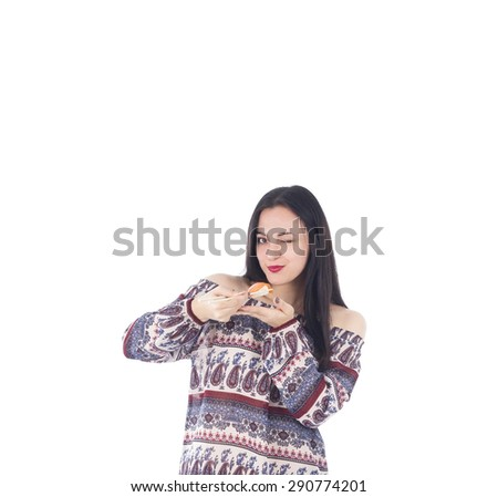 Young woman winking an eye while holding a piece of sushi against a white background - stock photo