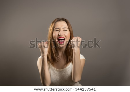 Young woman winner gesture. Winning success woman happy ecstatic celebrating being a winner.  - stock photo