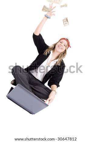 Young woman winning online flinging money in the air. Money (American dollars) is not in focus. - stock photo