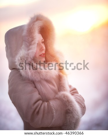 Young woman winter portrait. Red sunset light. - stock photo