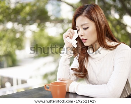young woman wiping tears with facial tissue.