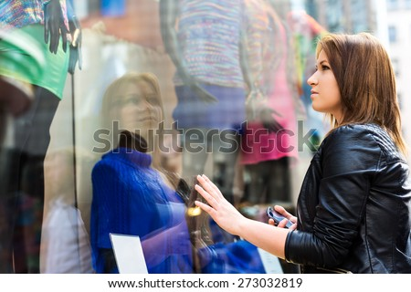 Young woman wistfully looking at the clothes in the shop window - stock photo