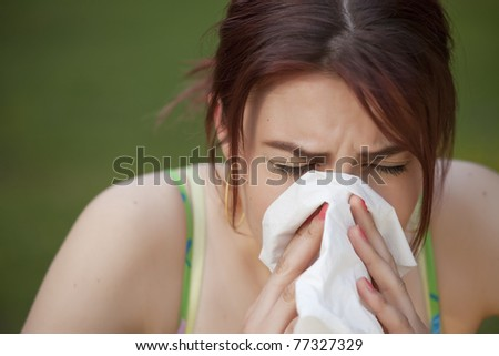 young woman with a an allergy sneezing into her handkerchief