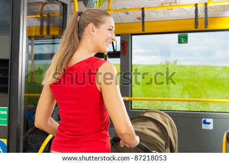 Young woman with a baby in a stroller getting into a bus on the bus station - stock photo