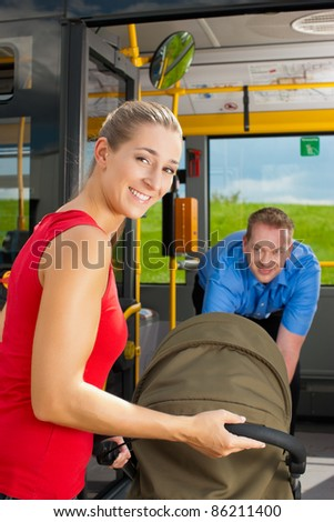 Young woman with a baby in a stroller getting into a bus on the bus station, the bus driver is helping her - stock photo