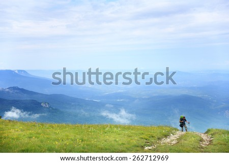 Young woman with a backpack and trekking poles walking on the path up the hill with green grass on the background of the beautiful mountain scenery under the blue summer sky with cloudscape - stock photo