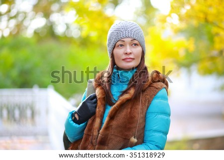 Young woman with a backpack standing near the fence in the park in autumn