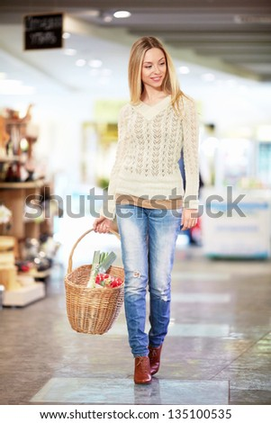 Young woman with a basket in a store
