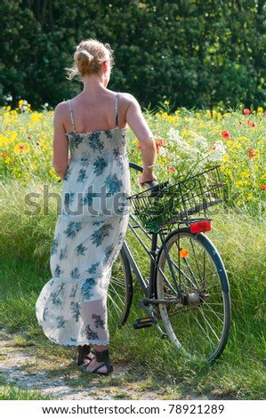 young woman with a bicycle in front of blooming rapeseed in early summer - stock photo