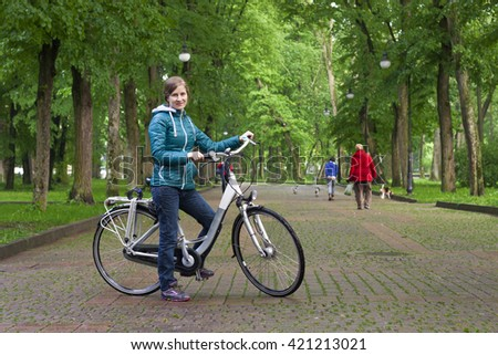 Young woman with a bicycle in the park green trees