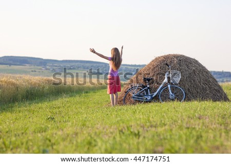 Young woman with a bicycle on field with haystacks on a sunny day - stock photo